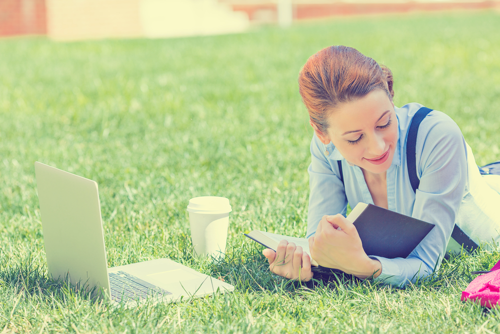 Girl lying on the grass with a laptop