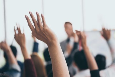 Audience raising hands to reflect students' views on teaching excellence framework